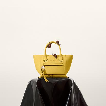 La nouvelle ligne cuir incarne une vision poétique du voyage cher à la Maison Longchamp. Pour l'Automne-Hiver 2020, Longchamp donne une nouvelle fois vie à sa vision du voyage en créant la ligne Mailbox. Un sac en cuir grainé sensuel et élégant. Un clin d'oeil subtil aux boîtes aux lettres (d'amour). Les mots doux se glissent dans la poche avant qui rappelle la fente d'une boîte aux lettres. Compagnon de voyage autour du monde, Mailbox est l'écrin de tous les courriers à garder.